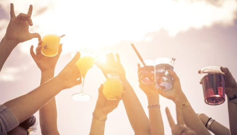 people holding up drink glasses in the sun