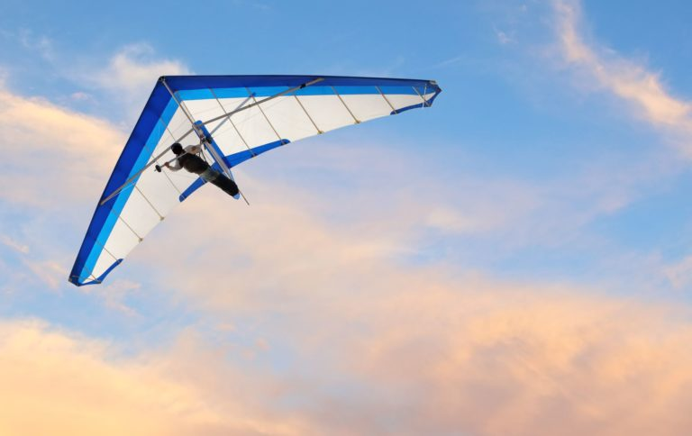 a person hang gliding in the sky