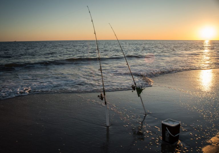 a couple of fishing rods in the surf