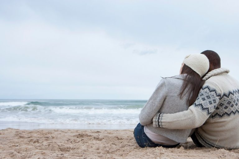 people wearing sweaters on the beach
